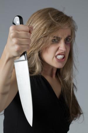revenge: Portrait image of an abused woman holding a sharp knife for revenge Stock Photo