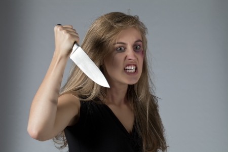 Close-up image of an angry lady grinding her teeth holding a knife on a gray background Stock Photo - 17377452