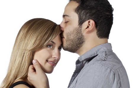 Close-up image of a couple while husband kissing the forehead of his wife photo