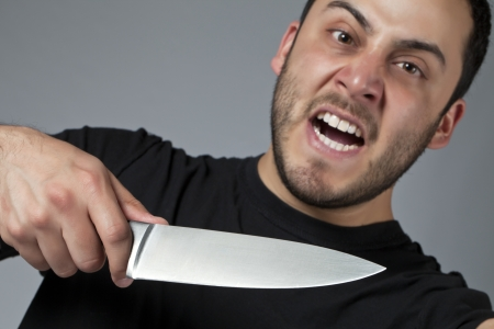 male killer: Close-up image of an angry male killer holding a knife over the gray background Stock Photo