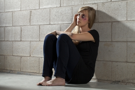 Image of a battered woman sitting on the floor and leaning on the wall photo