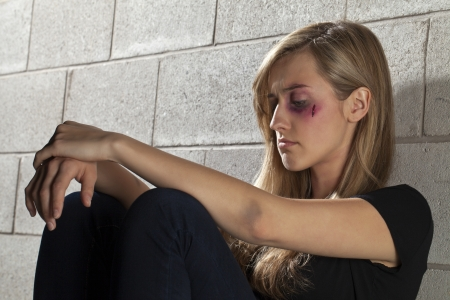 Image of battered young woman sitting and while leaning on the wall