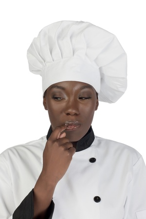 Portrait of a female African chef licking her finger photo