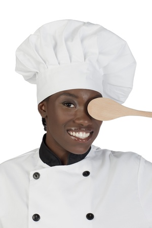 Female African chef covering her left eye using a wooden ladle photo