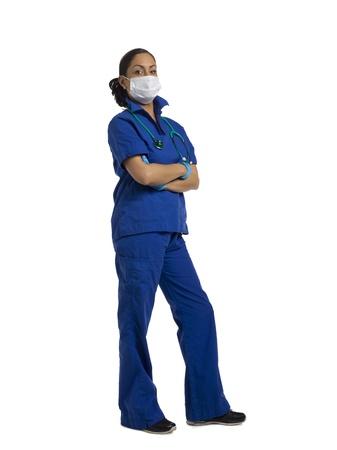 medical mask: Retrato de una enfermera con m�scara m�dica con el brazo cruzado sobre un fondo blanco Foto de archivo