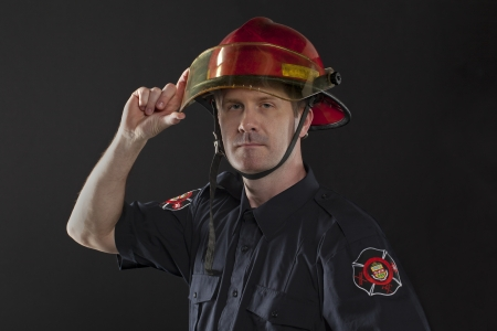 turnouts: Image of fireman holding his helmet against black background