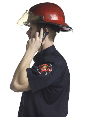 cb phone: Side view image of a fireman talking CB phone isolated on a white surface