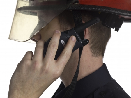 Image of fireman talking on portable radio against white background photo