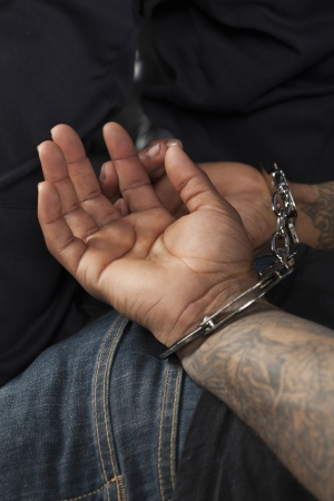 apprehended: Closed up man hands with handcuffs