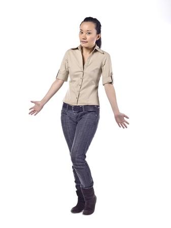 not full: Full length portrait of asian girl gesturing do not know sign against white background Stock Photo