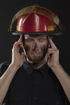 turnouts: Image of fireman trying to relax his self against black background Stock Photo