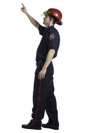 fire fighter: Full length portrait of male fire fighter pointing up against white background