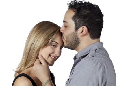 Image of an adult man kissing the forehead of his girl against white background photo