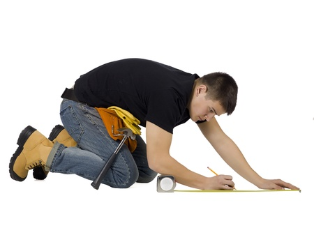 Close-up image of a carpenter lying on the floor measuring something Imagens
