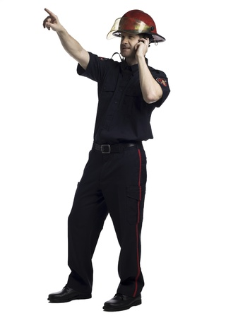 Full length image of a pointing fireman with radio Stock Photo