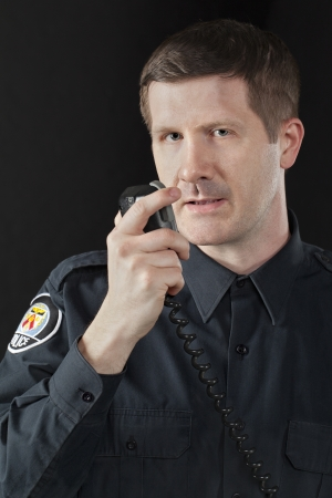 Close-up image of a handsome policeman talking on the cb phone radio Stock Photo - 17377513