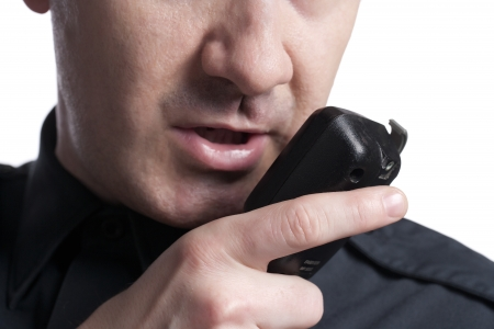 Unrecognized policeman talking on the cb phone radio isolated on a white surface Stock Photo - 17377448