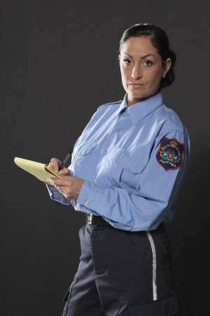 Portret van een mid-leeftijd politieagente met een nota en pen op een zwarte achtergrond
