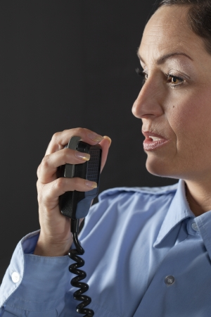 cb phone: Close up image of policewoman talking on cb phone