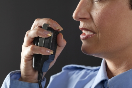 cb phone: Cropped image of policewoman with cb phone on black background