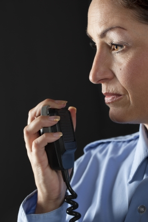cb phone: Close up image of policewoman with cb phone against black background