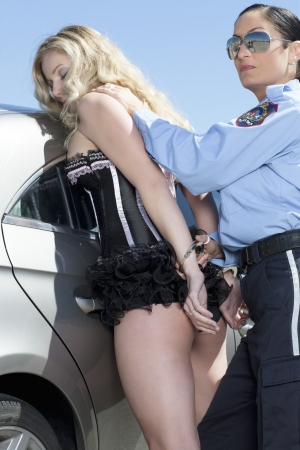 Portrait of police woman arrest a sexy lady against white background Stock Photo - 17377501