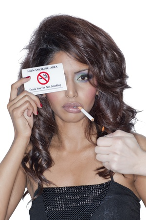 Close-up image of a rebellious woman smoking while holding a non-smoking area card photo