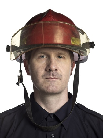 Portrait of serious fireman against white background photo
