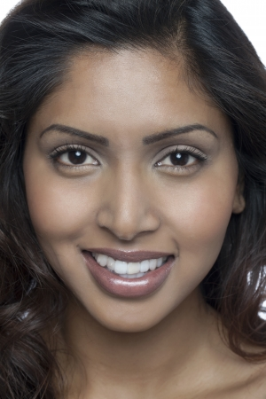 Close-up image smiling Indian woman looking at the camera against the white background photo