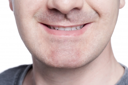Close-up image of unrecognized man smiling against the white surface Banco de Imagens