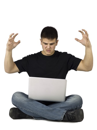 teenage guy: Portrait of stressed teenage guy looking his laptop against white background