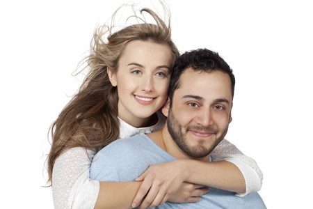 Sweet romantic couple smiling while looking at the camera against white background photo