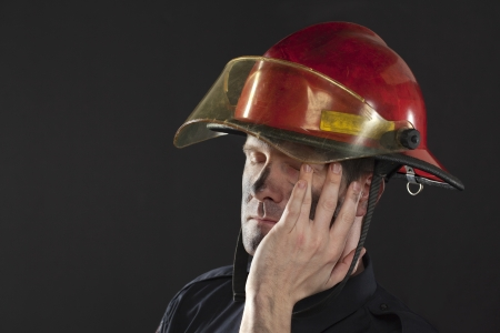 Closed up shot of a tired fireman over a black background photo
