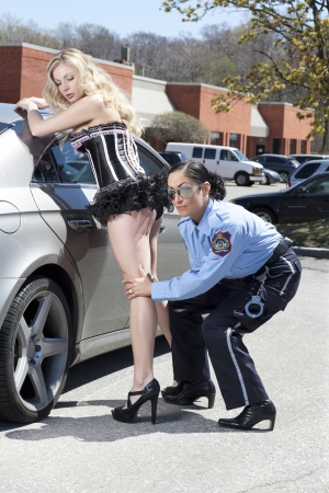 A sexy woman frisking by a police woman on a rural scene photo