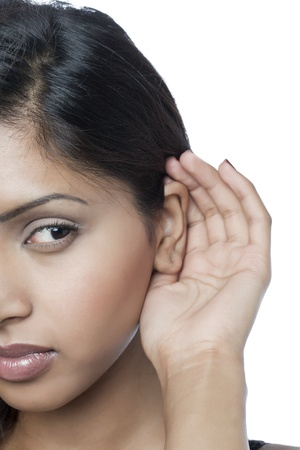 listening ear: Close up image of woman in listening gesture against white background