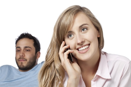 Woman talking on her cell phone with a jealous boyfriend on her back Stock Photo - 17377346