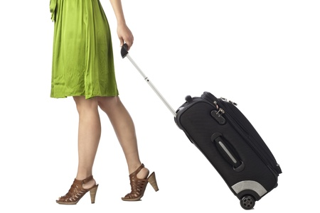 Unrecognized woman traveler pulling her luggage bag on a white surface photo