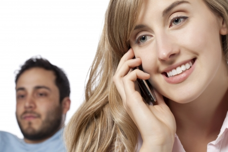 lovers quarrel: Image of woman talking to her phone with her jealous boyfriend in background Stock Photo