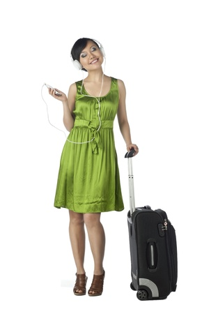 Portrait of a woman traveler listening to the music against the white surface photo