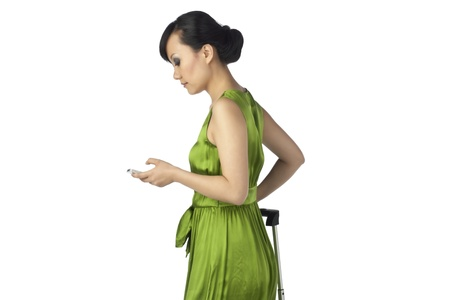 A woman traveler texting standing side view on the white background photo