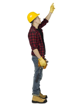 Full length portrait of young carpenter pointing up against white background
