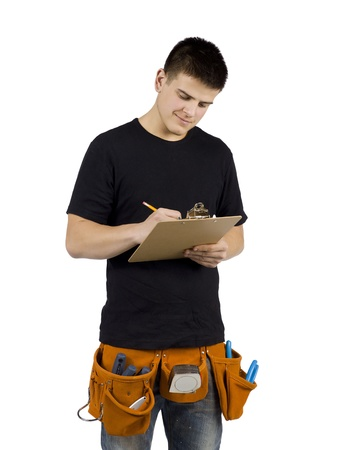 Portrait of young handyman writing something against white background