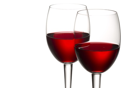 cropped shots: Close-up shot of red wine in wineglass against white background.