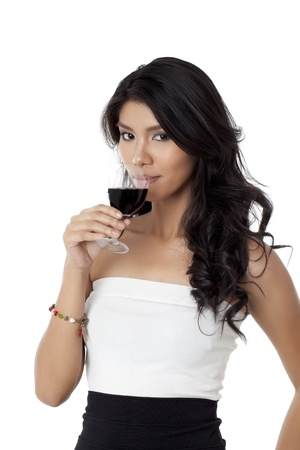 Beautiful asian woman drinking a glass of red wine