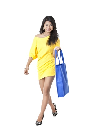 Portrait of an Asian woman on a sexy walk carrying a blue shopping bag photo