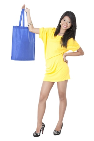 Portrait of an attractive Asian woman facing and smiling on camera carrying a shopping bag photo