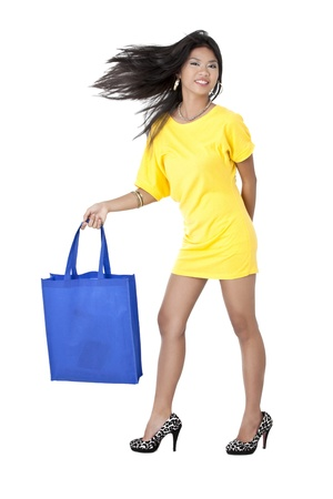 swept: Portrait shot of a attractive young woman wearing yellow dress posing with blue shopping bag. Model: Franchesca Lorraine M. Meris Stock Photo
