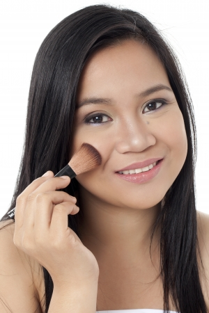 Close-up image of a beautiful lady with a make-up brush applying make-up