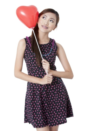 Portrait of a beautiful lady holding a heart shape balloon while looking upward Stock Photo