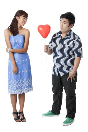 A guy gives red balloon to a girl against white background Stock Photo
